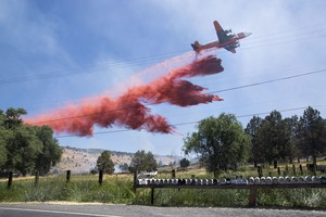 An air tanker dropsfire retardant on a fire that threatens homes and businesses along Highway 97 near Wocus, Oregon, July 19, 2017.