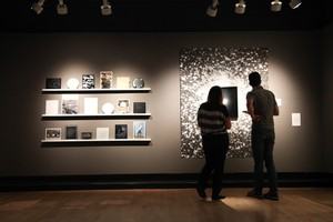 """Curator Julia Bradshaw describes artwork in the eclipse-inspired """"Totality"""" exhibit at the Fairbanks Gallery of Art to OPB's Aaron Scott in Corvallis, Oregon."""