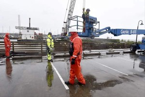 Workers operate on a pier in Astoria that is the likely source of an oil leak on the Columbia River.