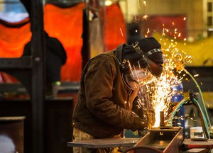A worker at Mohawk Metal grinds on a beam at the company's 35,000-square-foot facility in west Eugene. Amazon's new downtown Seattle headquarters features millions of pounds of steel from Mohawk Metal.