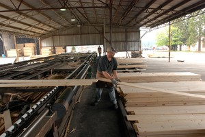In this April 25, 2013 photo, Otto Billitz stacks pine boards coming out of the planers at Rough & Ready Lumber Co. in O'Brien, Ore. The mill is the latest to close in timber country, where rural communities are still struggling to find their way to a new economy. But Anne Kubisch says there is hope for economic growth in the state's rural areas.