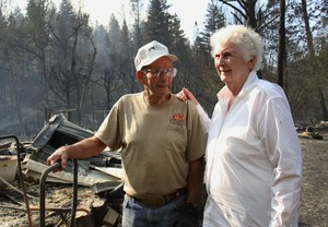 Dean and Betty Elliott look over the remains of their charred house. The Canyon Creek Fire destroyed their home of 53 years.