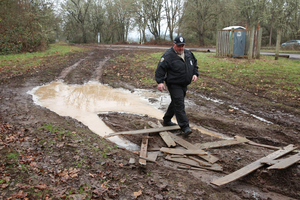 Lane County Parks Ranger Todd Bowen surveys a mud hole in the parking lot at Mount Pisgah, near Springfield.