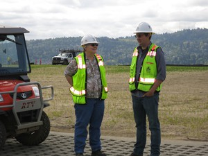 Portland Water Bureau engineers stand on top of a pair of new covered reservoirs at Kelly Butte.