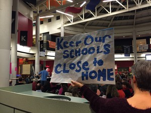"""A Beaverton parent holds up a sign that reads """"Keep Our Schools Close To Home."""" A boundary committee has been working to rewrite lines all over the district."""