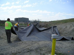 Contractors place an engineered cover, called geomembrane, over the balefill area at Pasco Sanitary Landfill. The fire under this area burned for about two years. Photo credit: John Richards