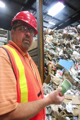 Keith Ristau, President of Far West Fibers, pulls a disposable coffee cup out of a pile of curbside recycling.