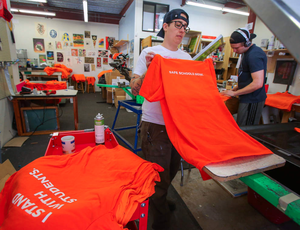 "Production manager Brit Howard screen-prints shirts at Threadbare Print House in Eugene, Ore. with the slogan ""I Stand With Students."""