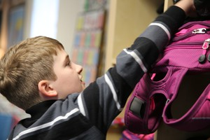 Class of 2025 student Johnathan grabs his backpack.