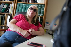 Teresa Christian sits back as she listens to a trained audio describer describe the eclipse as it passes through Nashville, Tennessee.
