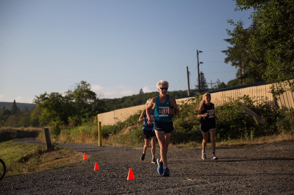 Runners in the Vernonia Marathon pass by Greenman Field on the Banks-Vernonia State Trail.