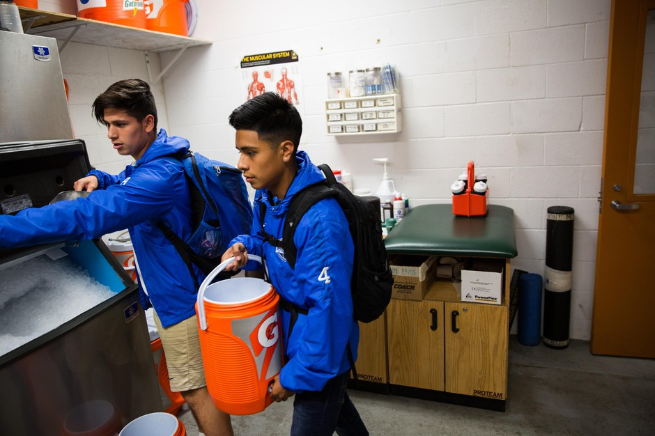 Angel Nuñez (right) and Noah Sanchez fill a Gatorade cooler with water and ice.