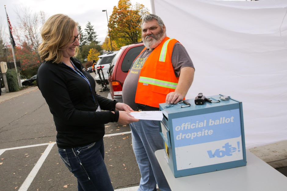 A voter drops off her ballot at the Washington County Elections Office in Beaverton, Ore. on Nov. 5, 2018.
