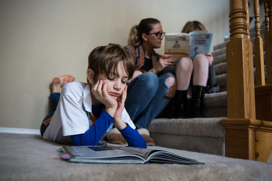 Ten-year-old Landon reads a book while his mother, Sarah McPartland, and sister, Vivian, read on the stairs at their home in Vancouver, Wa., Thursday, Feb. 28, 2019.