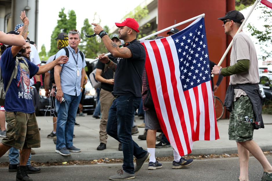 Patriot Prayer leader Joey Gibsondirects people back to the west side of the Willamette River during demonstrations in Portland, Ore., Saturday, Aug. 17, 2019.