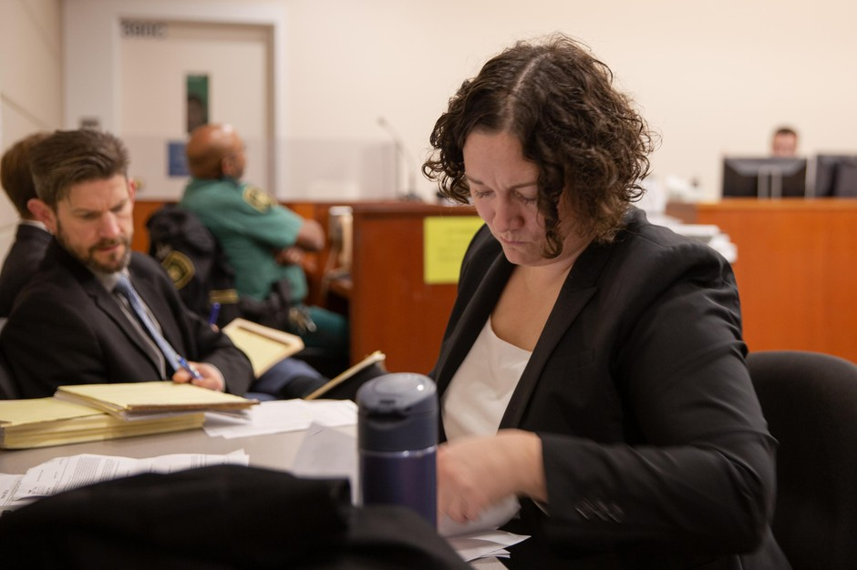Defense attorney Stacey Reding looks over documents during a court hearing Tuesday, Oct. 8, 2019, at the Multnomah County Justice Center in Portland, Ore. Reding said it's frustrating to be unable to provide clients in need of mental health treatment everything they need.