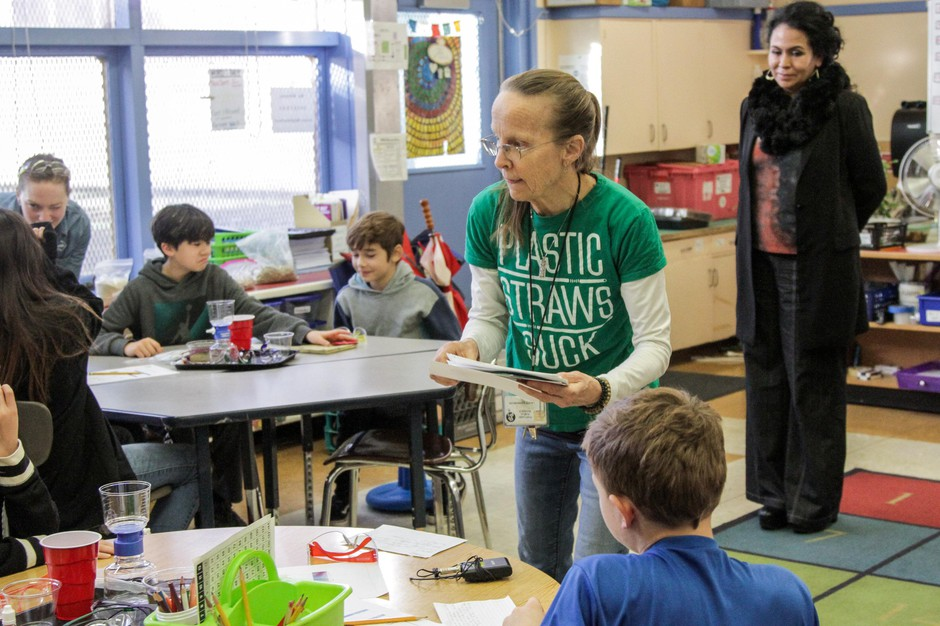 Teacher Laurie Shonkwiler passes out material for a water filtration experiment at Bridger K-8 in southeast Portland.