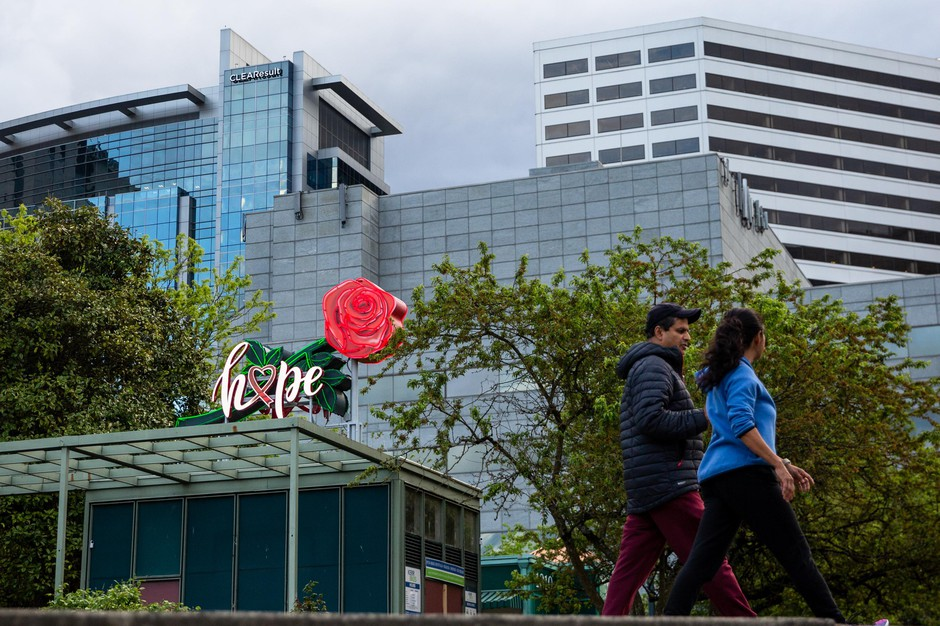 "People walk along the waterfront in Portland, Ore., Thursday, April 29, 2020. The word ""hope"" was placed on the neon rose sign in response to the COVID-19 pandemic."
