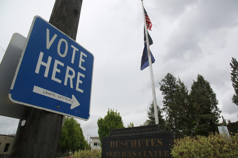 A sign points to a ballot box in downtown Bend, May 19, 2020.