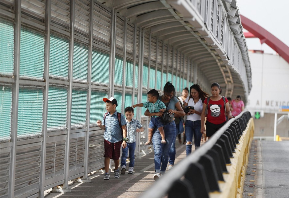 In this June 28, 2019, file photo, local residents with visas walk across the Puerta Mexico international bridge to enter the U.S., in Matamoros, Tamaulipas state, Mexico. A federal judge in Portland, Ore., on Saturday, Nov. 2, 2019, put on hold a Trump administration rule requiring immigrants prove they will have health insurance or can pay for medical care before they can get visas. U.S. District Judge Michael Simon granted a preliminary injunction that prevents the rule from going into effect Sunday.