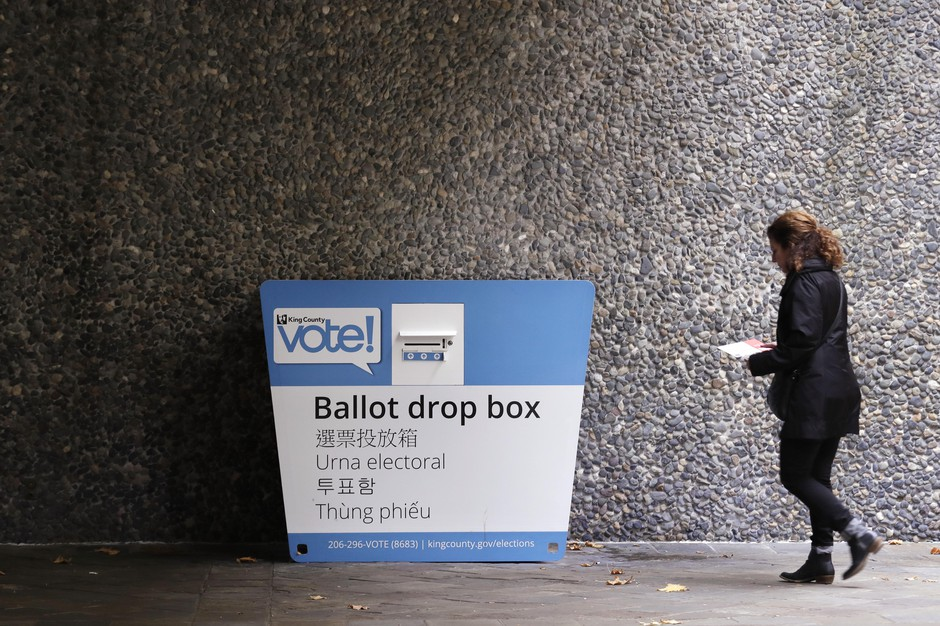 A voter heads to a ballot drop box Monday, Nov. 4, 2019, in Seattle.