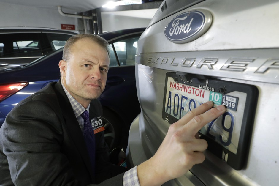 Tim Eyman, a career anti-tax initiative promoter, poses for a photo with the expired car registration tabs on his SUV, Tuesday, Nov. 26, 2019, in a parking garage in Seattle, following a hearing in King County Superior Court where lawyers for cities and counties across Washington state asked King County Judge Marshall Ferguson to block Eyman's $30 I-976 car tab measure, which was approved by voters in the last election, saying it was misleading and violates Washington's Constitution.