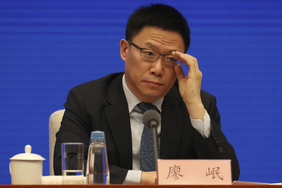 Liao Min, Deputy Director of the Office of the Central Commission for Financial and Economic Affairs and Vice Minister of Finance, adjusts his glasses during a press conference on the trade deal with the United States in Beijing on Friday, Dec. 13, 2019.