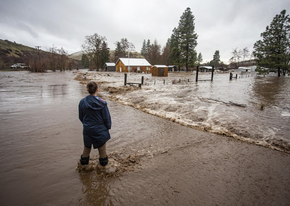 In this Thursday, Feb. 6, 2020, photo, Chantel Fuller watches as water floods her home in Thorn Hollow outside of Adams, Ore. Fuller's husband was involved in a rescue attempt that left him and three others stranded in the home as water from the Umatilla River rose around them Thursday evening, and were rescued by helicopter.