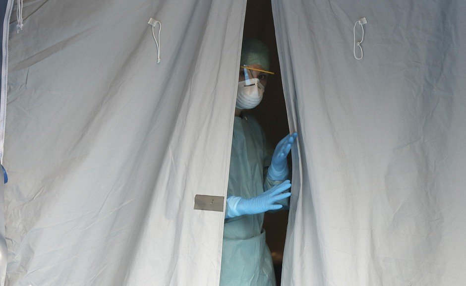 A medical staffer watches from a tent at one of the emergency structures that were set up to ease procedures at the Brescia hospital, northern Italy, Thursday, March 12, 2020.