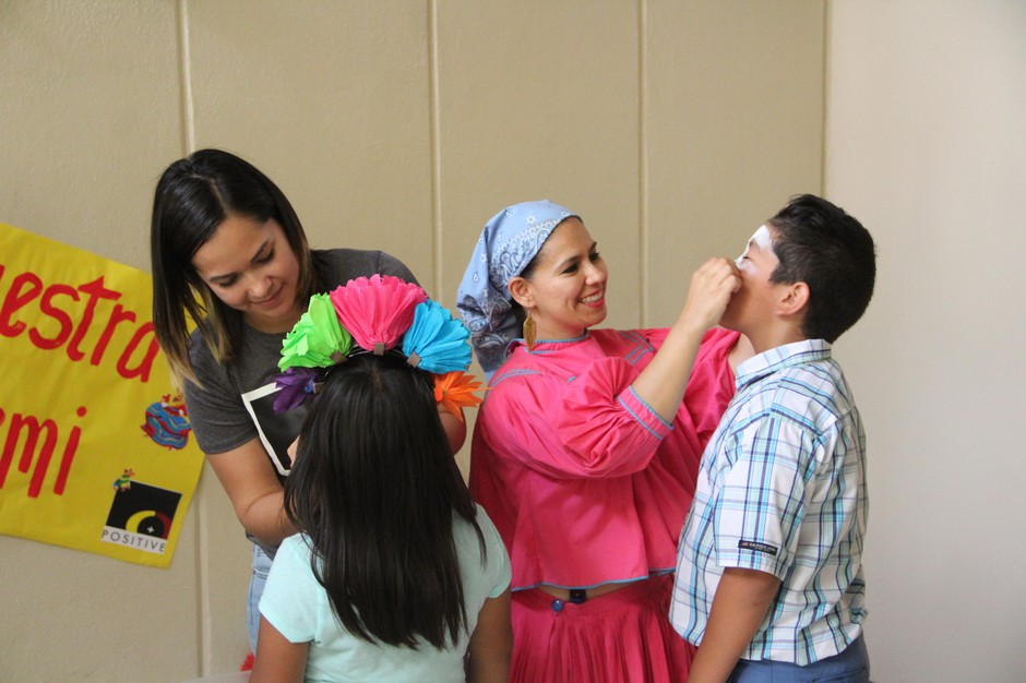 Binational teachers Marisol Ortega, right, and Noemi Espinoza paint the faces of two summer school students during the parent night at Ontario High School on July 10, 2019.