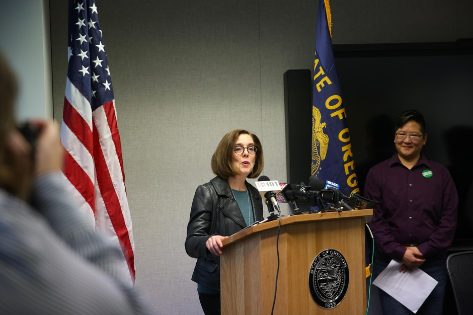 Oregon Gov. Kate Brown signs an executive order Oct. 25, 2019, to strengthen state protections for LGBTQ+ people.