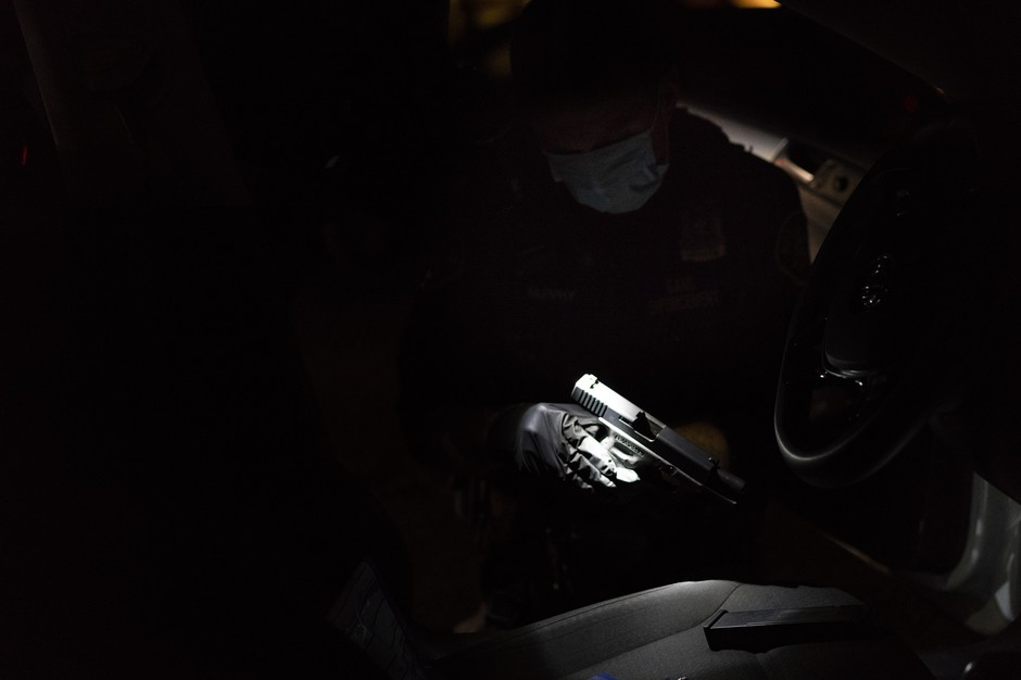 Officer Patrick Murphy swabs a handgun which he and the Gang Enforcement Team found in a car with three individuals in front of a high school homecoming football game in Northeast Portland on Sept. 21, 2018, in Portland, Oregon.