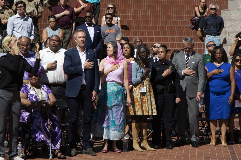 Mayor Ted Wheeler and other city officials stand for the National Anthem at Pioneer Courthouse Square during a press conference to denounce violence Aug. 14, 2019.
